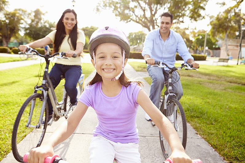 Little girl riding a bike with her parents riding bicycles behind her outside