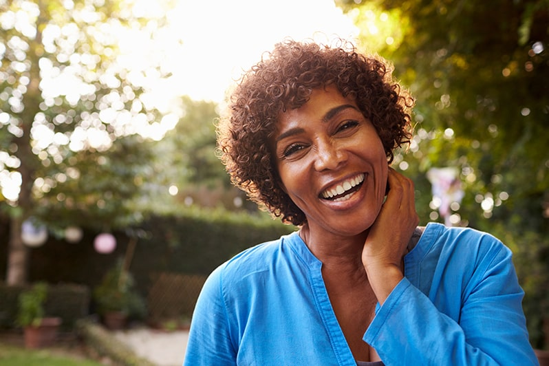 Aligned right image of woman outside with curly hair smiling, hand on side of face