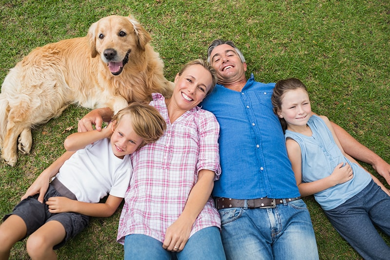 A dog, son, mom, dad, and daughter laying in the grass together smiling