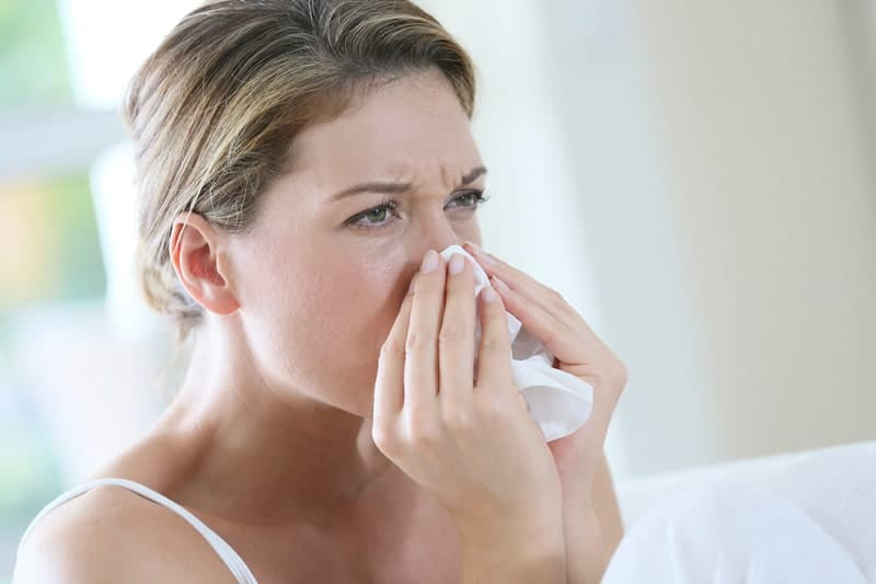 Woman blowing nose into a tissue