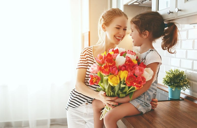 Mom holding daughter sitting on counter with a bounquet of flowers in their hands
