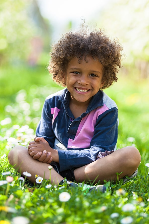 Young child sitting criss-cross in the grass with blurry background