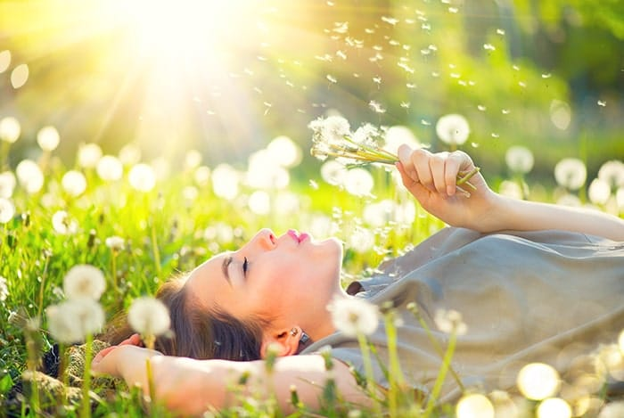 A girl laying in the grass blowing dandelions to the sky on sunny day